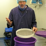 David Lea-Wilson demonstrates how the salt flakes are graded by hand using sieves.